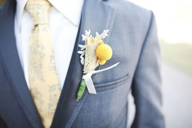 a chic grey suit spruced up with a billy ball boutonniere and a printed yellow tie