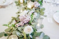 11 a lush table garland with pink and white blooms and candles for a fresh spring feeling