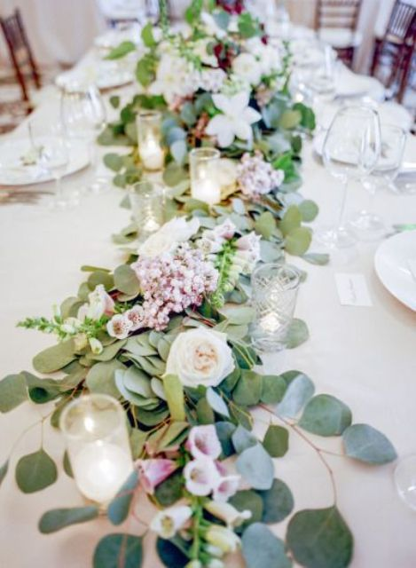 a lush table garland with pink and white blooms and candles for a fresh spring feeling