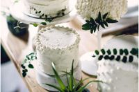 11 an assortment of white textural wedding cakes with fresh greenery on top