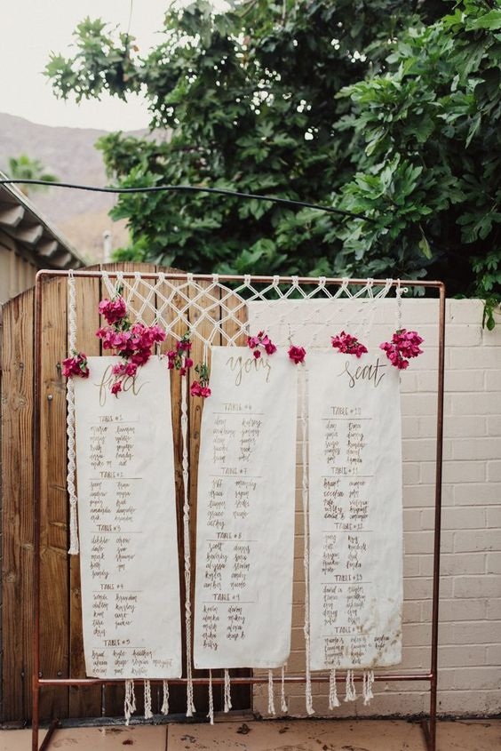 a boho woven seating chart with bold pink blooms on a copper frame for a colorful touch