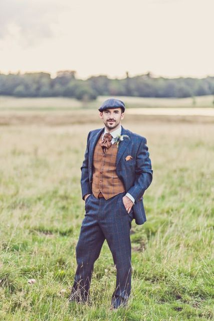 a navy windowpane wedding suit, a brown vest, a vintage tie and a cap for a styled look