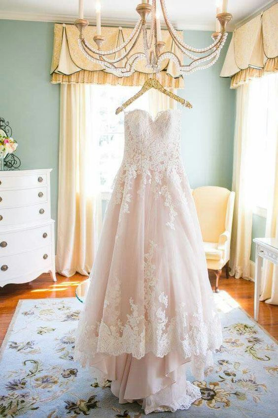 a princess-styled light pink wedding dress with white lace appliques on the bodice and skirt trim