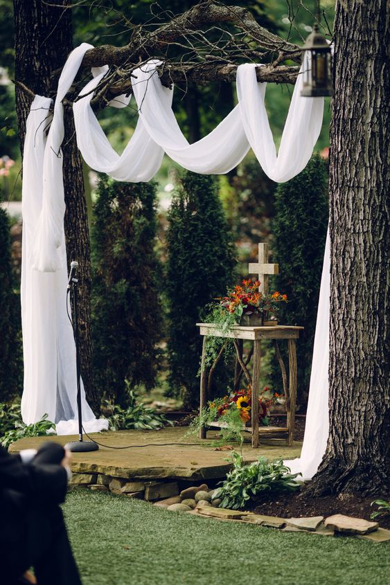 branches decorated with airy fabric, an altar with a cross and some blooms