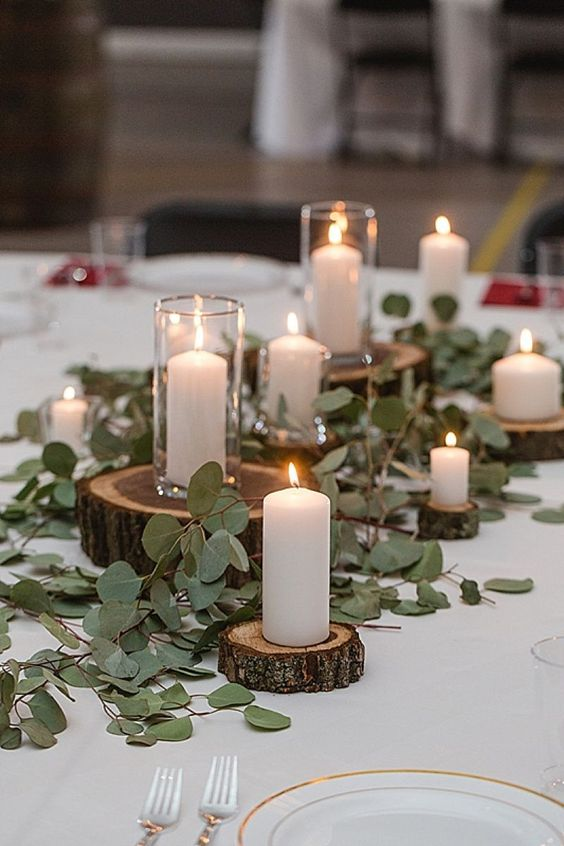 rustic centerpiece with greenery, wood slices and pillar candles for an elegant rustic tablescape