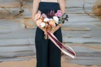 13 a black spaghetti strap jumpsuit and a colorful bouquet for a tropical wedding
