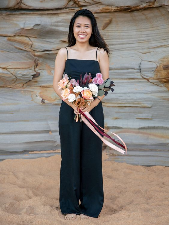 a black spaghetti strap jumpsuit and a colorful bouquet for a tropical wedding