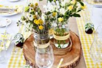 13 a bold rustic table setting with a checked yellow runner, wood slices and bold yellow blooms for the centerpiece