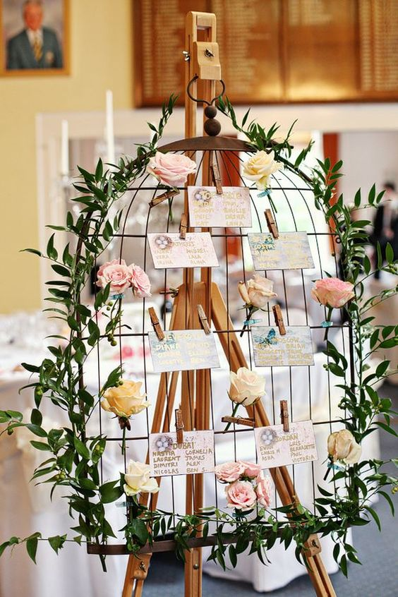 a chic birdcage-styled seating chart with fresh roses, greenery and floral escort cards attached