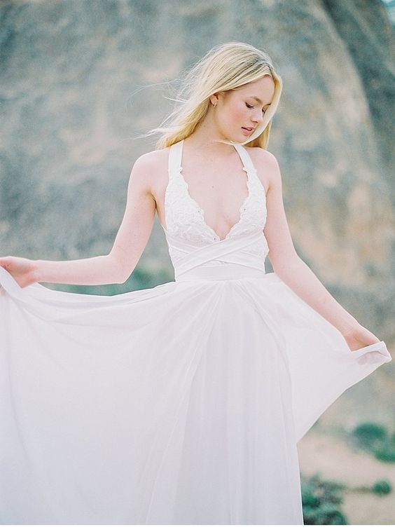 a chic wedding dress with thick halter straps, a lace bodice with a deep neckline and a bandage detail plus a flowy skirt