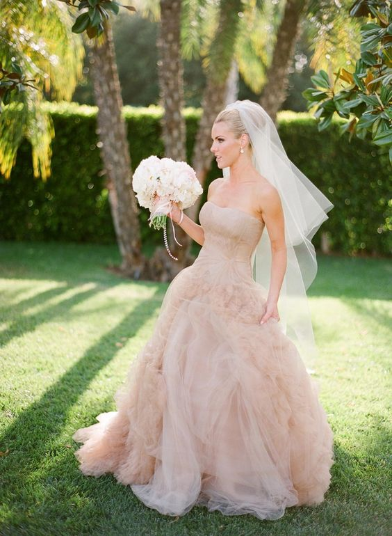 a strapless dusty pink wedding dress with a wrapped bodice, a layered tulle skirt for a formal bridal look