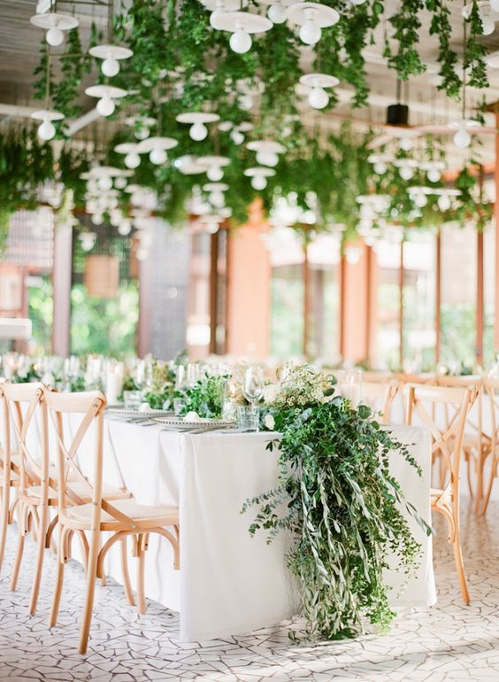 a very lush and textural greenery table runner and hanging greenery turn the space into a spring one
