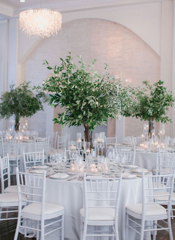 a white reception space done with lush and textural greenery centerpieces