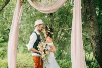 13 an improvised wedding arch of a branch, blush fabric, a lush floral garland and a glam chandelier