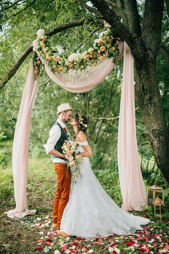 an improvised wedding arch of a branch, blush fabric, a lush floral garland and a glam chandelier