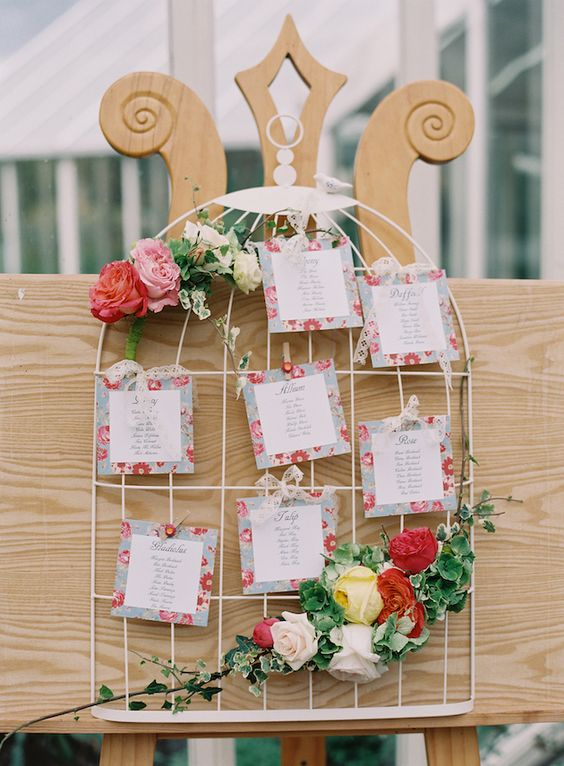 a cute bird cage with bright blooms and greenery and floral escort cards