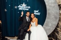 14 a cute photo booth setting with a crescent moon and stars and matching props for a wedding