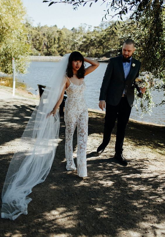 a lace jumpsuit on spaghetti straps and a veil for a unique and personalized bridal look