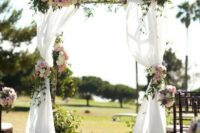 14 a rustic outdoor wedding arch decorated with lush florals and fresh greenery plus ethereal fabric