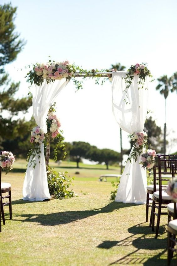 a rustic outdoor wedding arch decorated with lush florals and fresh greenery plus ethereal fabric