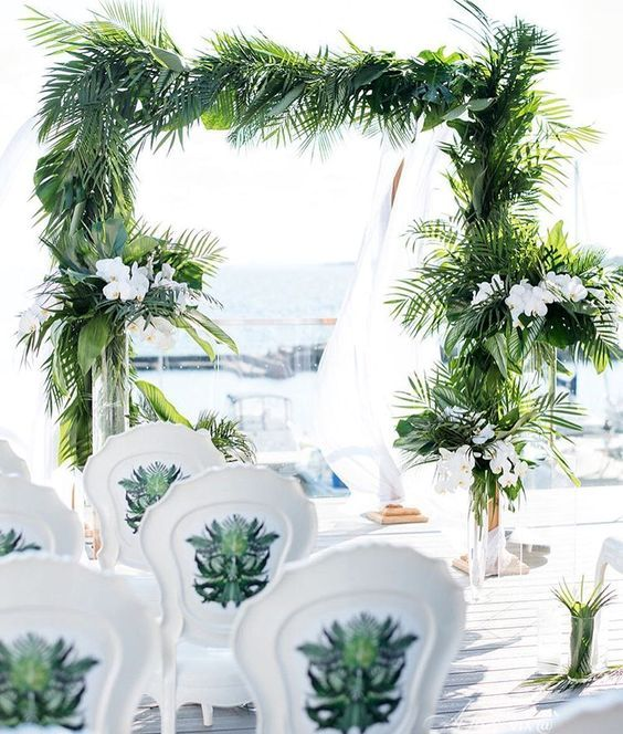 a tropical beach wedding ceremony with lush tropical leaves and white orchids