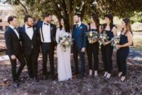 14 black jumpsuits with bow ties on the shoulders for bridesmaids and black tuxedos for groomsmen