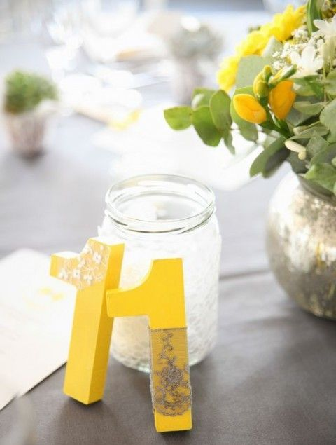 bold yellow table numbers decorated with white and grey lace and a mercury glass vase with yellow blooms