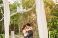 14 some semi sheer fabric and a glam chandelier on a tree branch to create a cute ceremony arch