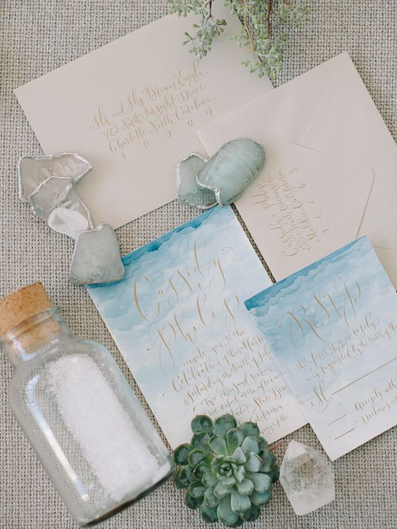 a chic coastal or beachside wedding invitation suite with watercolor invites in blues