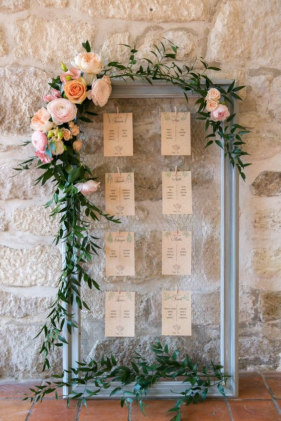 a frame with mesh and a seating chart, lush greenery garlands and large blooms on top