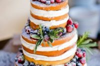 15 a naked wedding cake with fresh greenery and sugared berries on top is ideal for a rustic wedding