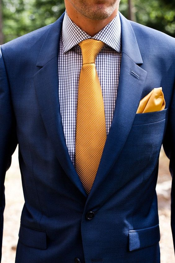 a preppy groom's look with a printed shirt, a blue suit, a yellow tie and a handkerchief instead of a boutonniere