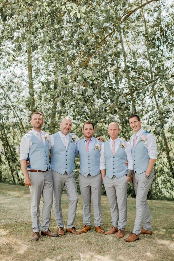 groomsmen wearing pink ties and blue vests with grey pants for a summer feel