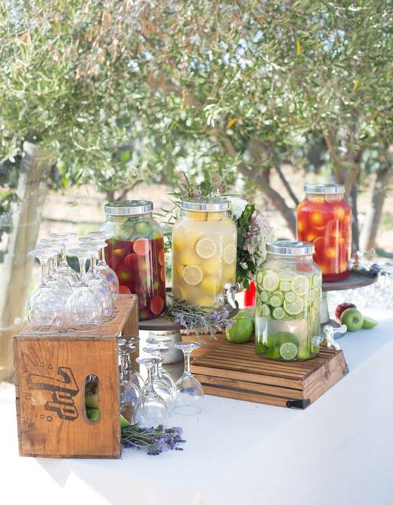 a rustic wedding bar with crates and wooden stands and simple drink tanks