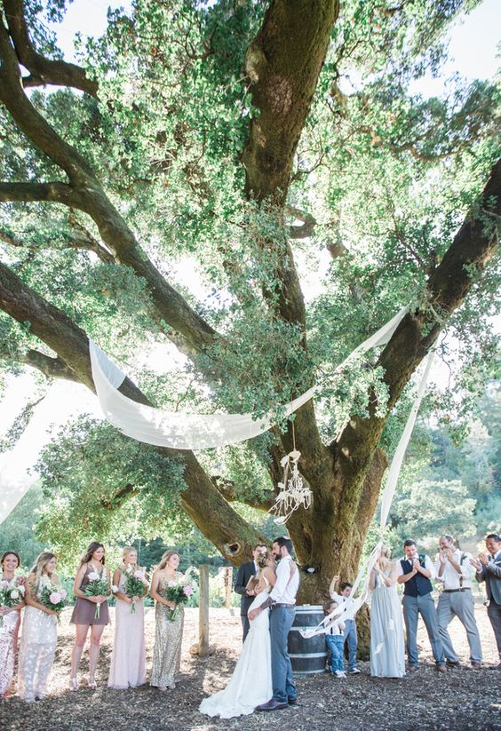 a sheer fabric garland hanging on a tree and a glam chandelier are all you need for a cool ceremony space