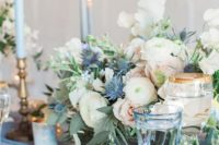 16 a summer table setting with blue candles, plates and glasses and a floral centerpiece with blue thistles and blush blooms