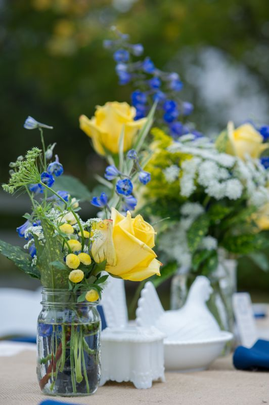 a wedding centerpiece of blue and yellow flowers in a mason jar is a cute idea for a rustic wedding