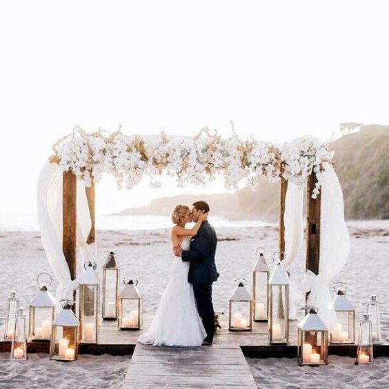 lush white flowers and lanterns and the finished look with the risers in the sand