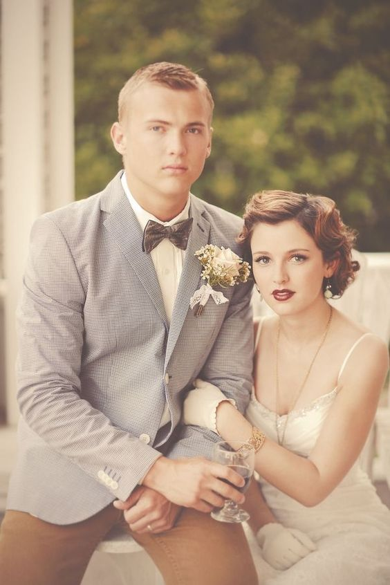 rust-colored pants, a white shirt, a grey jacket, a grey velvet bow tie for a 1920s inspired wedding