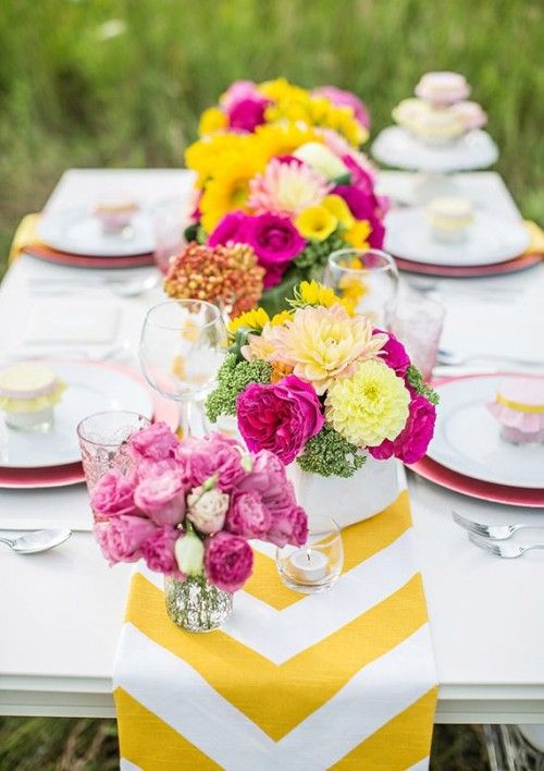 a bold yellow and white chevron table runner plus bright floral centerpieces for those who love bold colors