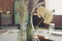 17 a cute rustic centerpiece with herbs, flowers, driftwood and candles in it