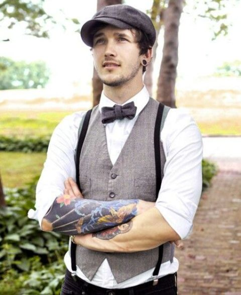 a dapper groom's look with a grey vest, black pants and suspenders, a bow tie and a cap