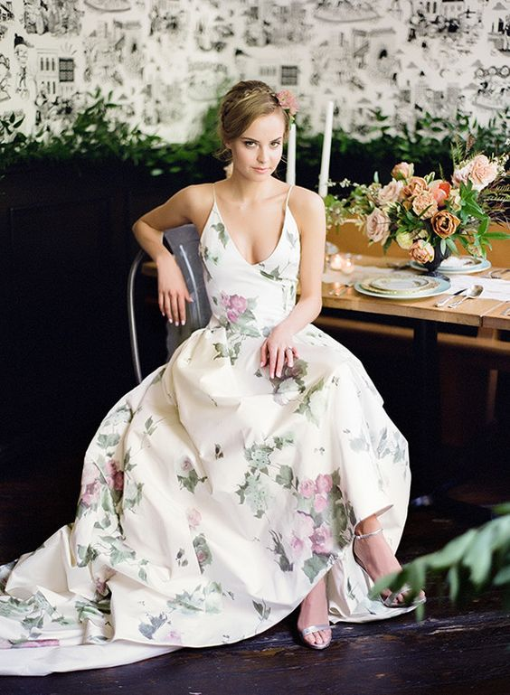 a pastel floral print wedding dress with a V neckline, straps and an A line silhouette for a garden wedding
