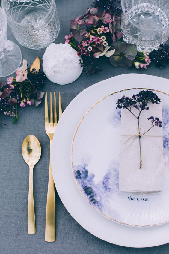 a woodland wedding tablescape done in pink and purple hues with some wildflowers