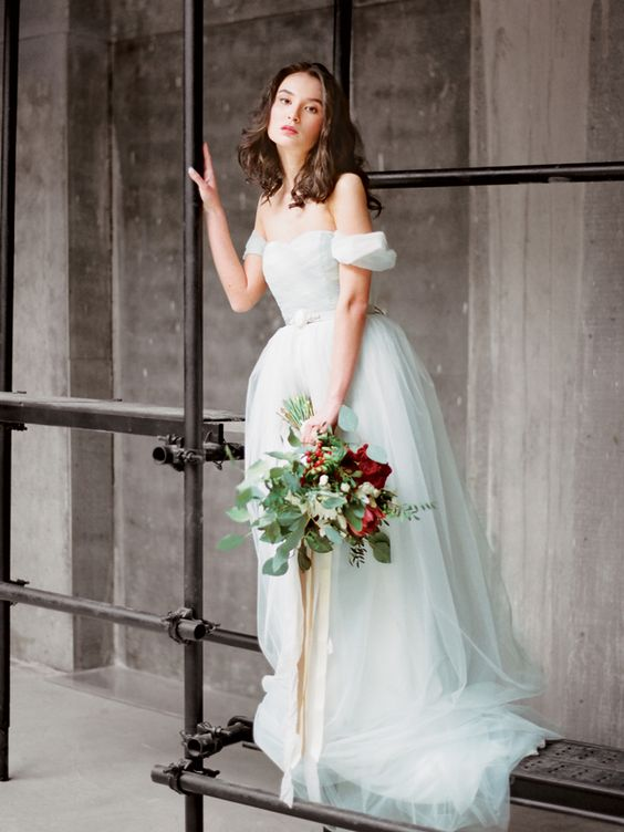 a light blue off the shoulder A-line wedding dress with an embellished belt and a full skirt