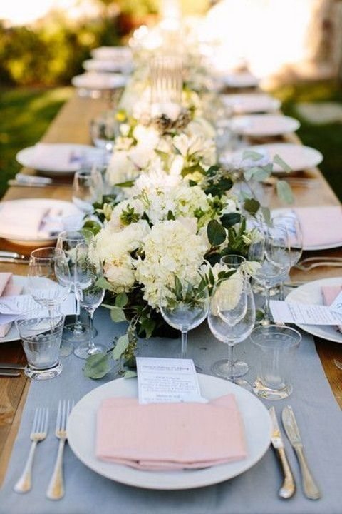 a powder blue wedding table runner, light pink napkins and neutral blooms for a chic look