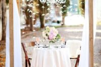 18 a rustic sweetheart table with an arch and ethereal fabric and paper flowers hanging