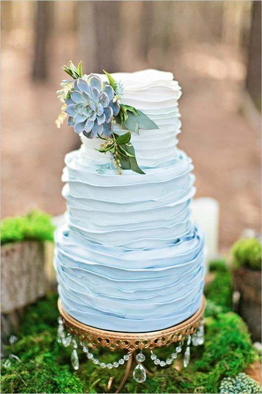 a textural ombre blue wedding cake with greneery and a large succulent on top for something blue