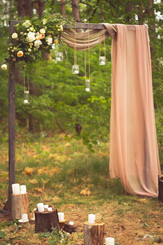 a wedding arch in the forest, candles, lush florals and a dusty pink ethereal fabric piece