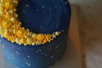 19 a blue wedding cake topped with a yellow crescent moon made of candies and meringues